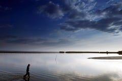 Fischer auf dem tropischen Strand im Abendhimmel Stockbilder