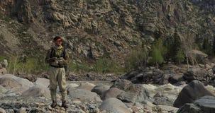 Fischer auf den Steinen fangen Fische im rauen Wasser stock footage