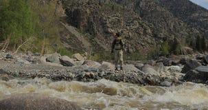 Fischer auf den Steinen fangen Fische im rauen Wasser stock video