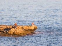Fischer auf der Klippe am frühen Morgen Stockbilder