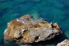 Fischer auf einem Felsen Stockfotografie