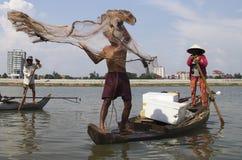 Fischer auf einem hölzernen Lastkahn mit Netz auf dem Fluss Lizenzfreie Stockfotos