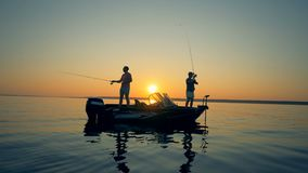 Fischer auf einem Sonnenunterganghintergrund, Seitenansicht stock video footage