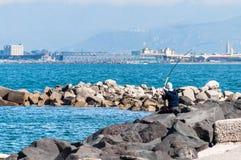 Fischer auf Felsen stockfoto