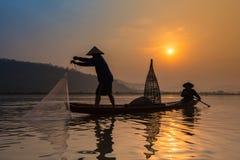 Fischer auf Fluss bei Sonnenaufgang lizenzfreies stockfoto