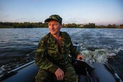 Fischer auf Gummimotorboot schwimmt auf den See liebhaberei lizenzfreie stockfotografie
