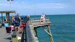 Fischer auf Kure setzen Pier auf Ostküste North Carolina auf den Strand stockbilder