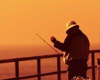 Fischer auf Pier am Sonnenuntergang lizenzfreie stockbilder