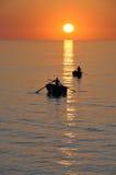 Fischer auf schönem ruhigem Schacht am Sonnenaufgang Lizenzfreies Stockbild