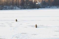 Fischer auf schneebedecktem Eis auf dem Fluss lizenzfreie stockbilder