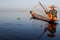 Fischer auf seinem Boot mit einem Fischnetz Stockfoto
