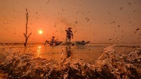 Fischer, der auf einem Fischerboot für einen Fisch im Wasser steht Lizenzfreies Stockfoto