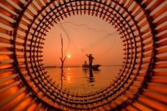 Fischer, der auf einem Fischerboot für einen Fisch im Wasser steht lizenzfreie stockfotos