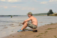 Fischer, der auf einer Küste sitzt stockfotografie