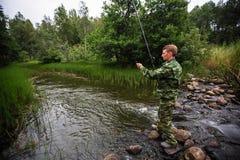 Fischer, der auf Steinfangenfischen auf dem Fluss steht liebhaberei stockfotos