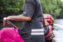 Fischer, der ein Boot des langen Schwanzes fährt stockfotografie