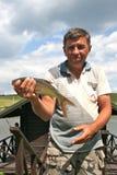 Fischer, der einen Fisch hält Lizenzfreies Stockfoto