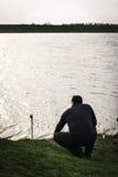 Fischer, der seine Stange überprüft Stockbilder