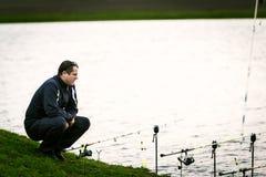Fischer, der seine Stangen warten auf einen Fisch betrachtet Stockbild