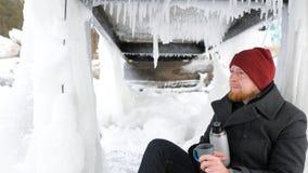 Fischer des jungen Mannes, der mit einer Thermosflasche auf dem See und dem trinkenden Tee sitzt lizenzfreie stockfotografie