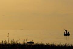 Fischer, die auf Strand während bei des Sonnenuntergangs fischen Stockfotos