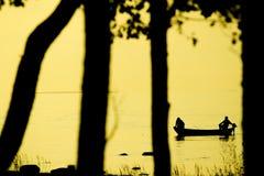 Fischer, die auf Strand während bei des Sonnenuntergangs fischen Lizenzfreies Stockfoto