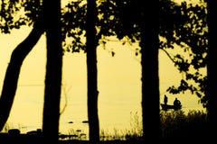 Fischer, die auf Strand während bei des Sonnenuntergangs fischen Lizenzfreie Stockfotos