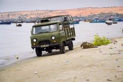 Fischer, die Auto auf Strand mit bunten Fischerbooten am 7. Februar 2012 in Mui Ne, Vietnam fahren Lizenzfreie Stockfotos