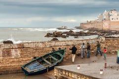 Fischer, die ihr Boot das Wasser herausziehen Stockbild