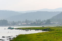 Fischer, die im Wasser nahe Brett und altem russischem Dorf stehen lizenzfreies stockbild