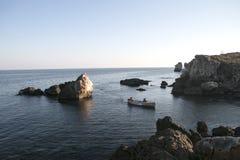 Fischer, die nach Hause mit dem Boot im Sonnenuntergang gehen Lizenzfreie Stockfotografie