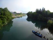 Fischer in einem Boot auf einem ruhigen Gebirgsfluss, Stadt Plav, Montenegro lizenzfreie stockfotografie