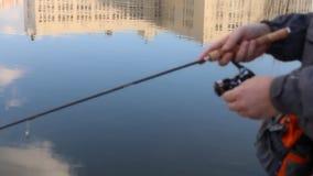 Fischer fängt einen Fisch auf dem Ufer von Fluss stock video footage