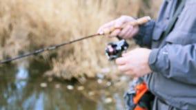 Fischer fängt einen Fisch auf dem Ufer von Fluss stock video