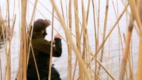 Fischer fängt einen Fisch auf dem Ufer von Fluss stock footage