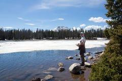 Fischer fängt einen Fisch in einem aufgetauten Flecken des Eises auf Lost See Stockbilder