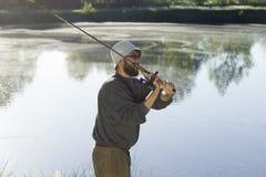 Fischer fängt Fische für das Spinnen Er leckt den Köder Stockfoto