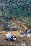 Fischer fischt auf Seestein, Spitzenvertikale Lizenzfreie Stockbilder