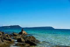Fischer fischt an KOH rong Bucht Kambodscha und sitzt auf Steinen am Strand stockbilder
