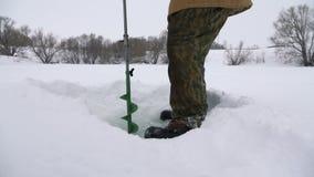 Fischer, gebohrtes Loch auf dem schneebedeckten See auf der Suche nach einem guten Fischereiplatz stock video
