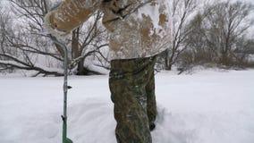 Fischer, gebohrtes Loch auf dem schneebedeckten See auf der Suche nach einem guten Fischereiplatz stock video footage