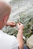 Fischer hält einen Haken und einen Wurm lizenzfreie stockbilder