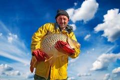 Fischer Holding ein großer Fisch gegen blauen Himmel und Wolken lizenzfreies stockbild
