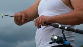 Fischer konfiguriert die seine Angelrute stock footage