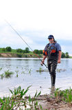 Fischer mit dem Spinnen auf die Bank des Flusses. Stockfotos
