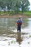 Fischer mit dem Spinnen in spezielle Kleidung. Lizenzfreie Stockfotos