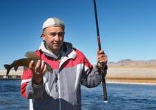 Fischer mit einem Fisch stockfoto