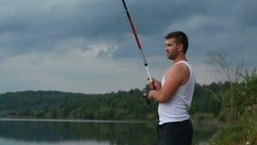 Fischer mit einer Angelrute auf dem Ufer des Sees am Abend stock video