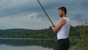 Fischer mit einer Angelrute auf dem Ufer des Sees am Abend stock footage