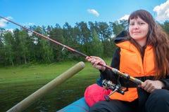 Fischer mit einer Angelrute im Boot Stockfoto